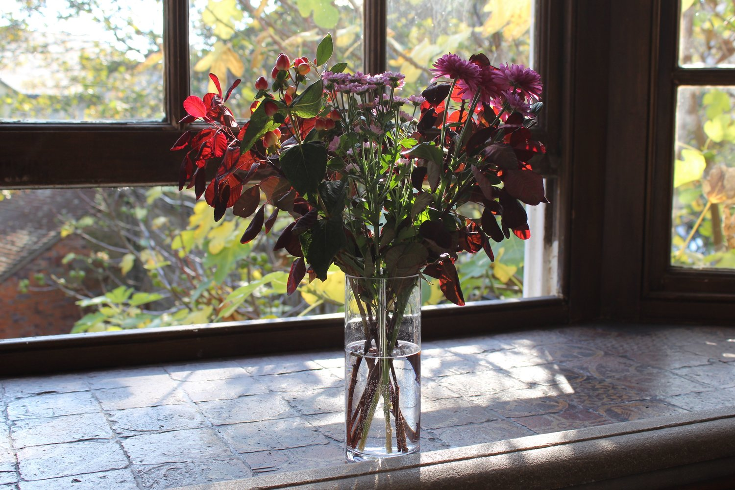 glass of brown flowers_leaves with open window